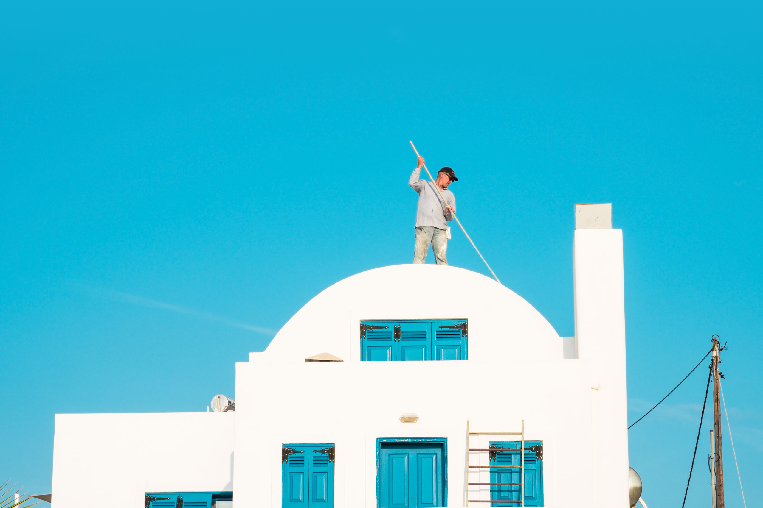 A man painting the roof in Santorini, Greece. Photo by Jari Anttonen.